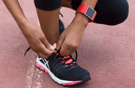 A close up of a woman tying her running shoe laces