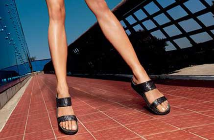 A pair of legs wearing black wide strap sandals