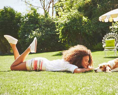 Woman lying on the grass with a puppy